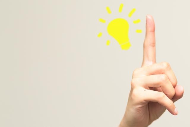 電球と指差ししている手